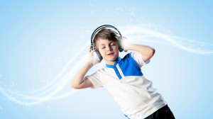Little cute boy in headphones with eyes closed enjoying music