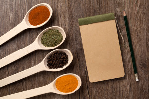 notebook and pencil for recipes and spices in spoons on wooden t