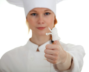 wounded female cook in white uniform and hat - cooking accident