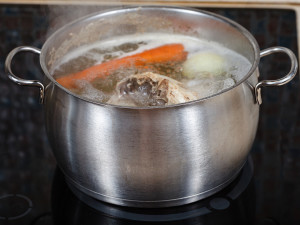 Simmering Chicken Soup In Pot On Cooker Close Up